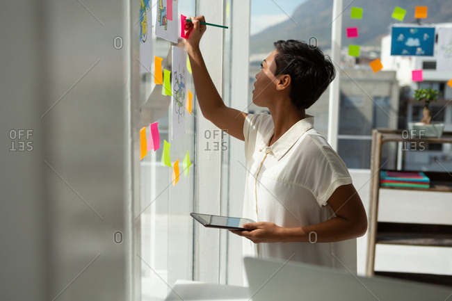 Side view of business executive writing on sticky note in office