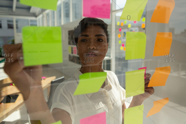 Business executive working on sticky notes in office