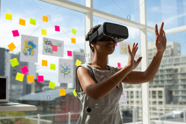 Female business executive using virtual reality headset in office