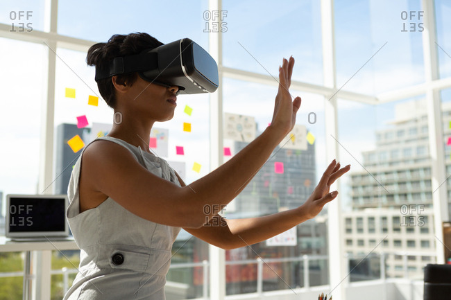 Side view of business executive using virtual reality headset in office