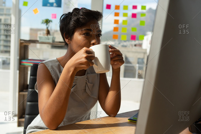 Female business executive having coffee while working in office