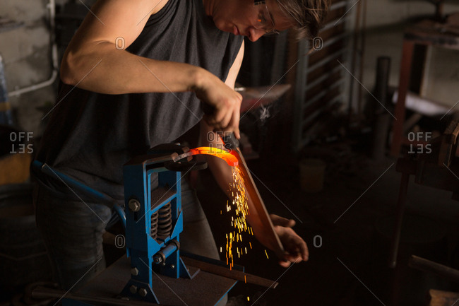 Attentive female metalsmith shaping horseshoe in factory