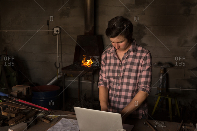 Female metalsmith using laptop in factory
