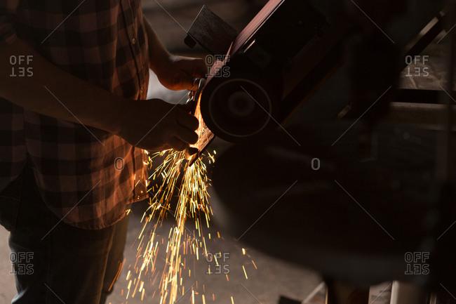Female metalsmith using sharpening machine in factory
