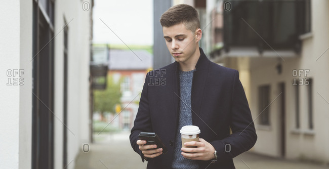 Young man using mobile phone while having coffee