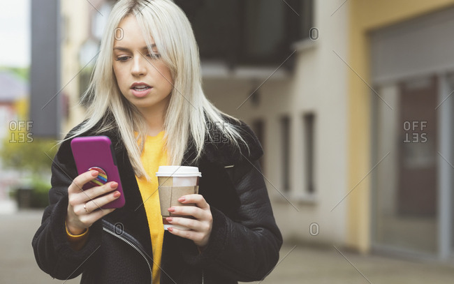 Beautiful woman using mobile phone while having coffee