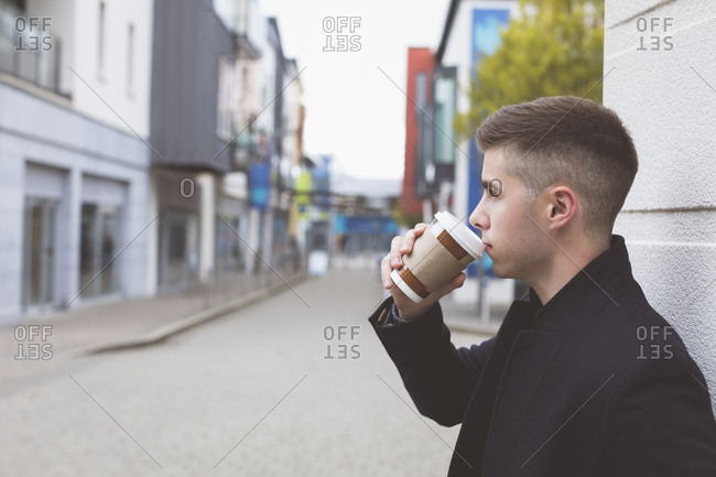 Side view of man having coffee in city