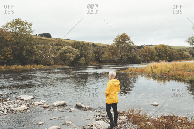 Rear view of woman standing near river