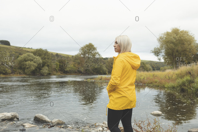 Side view of woman standing near river
