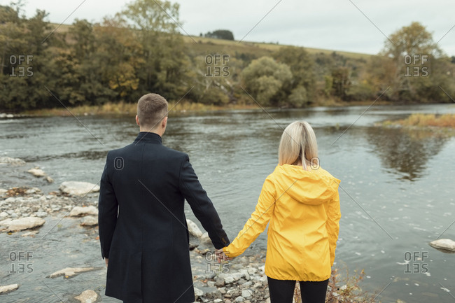 Rear view of couple holding hand and standing near river