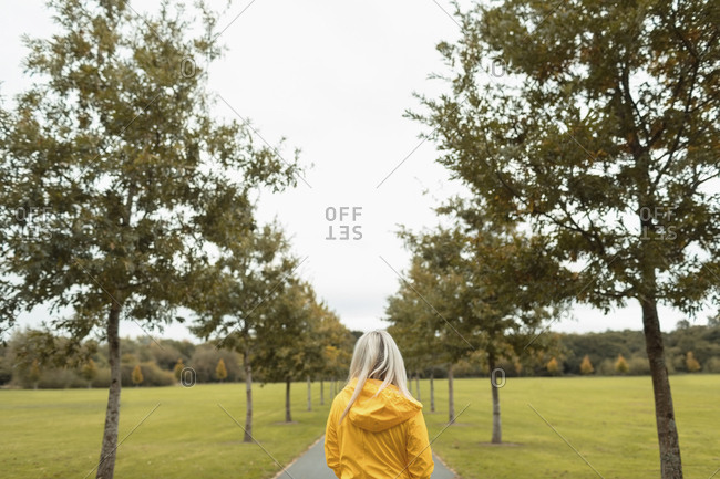Rear view of blonde woman walking in park