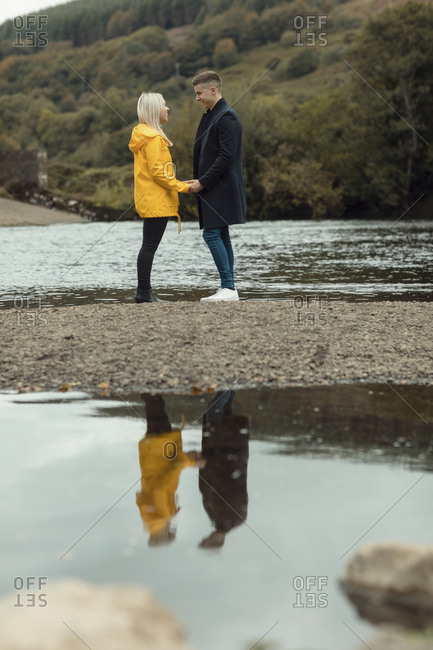 Happy couple holding hands near river