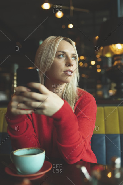 Woman looking away while using mobile phone in cafe