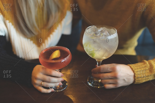 Close-up of couple holding cocktail glass in restaurant