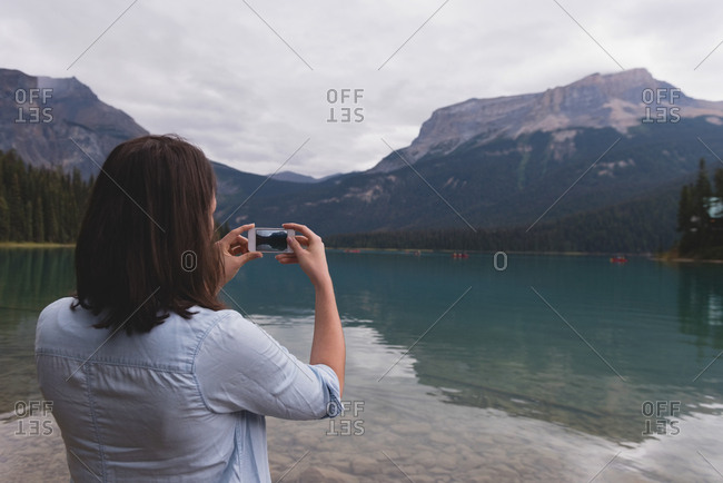 Rear view of woman clicking photos with mobile phone near lakeside