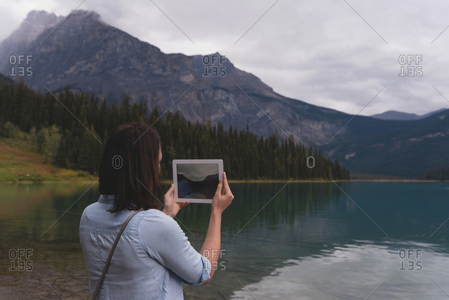 Rear view of woman clicking photos with digital tablet near lakeside
