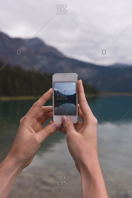 Close-up of woman clicking photos with mobile phone near lakeside