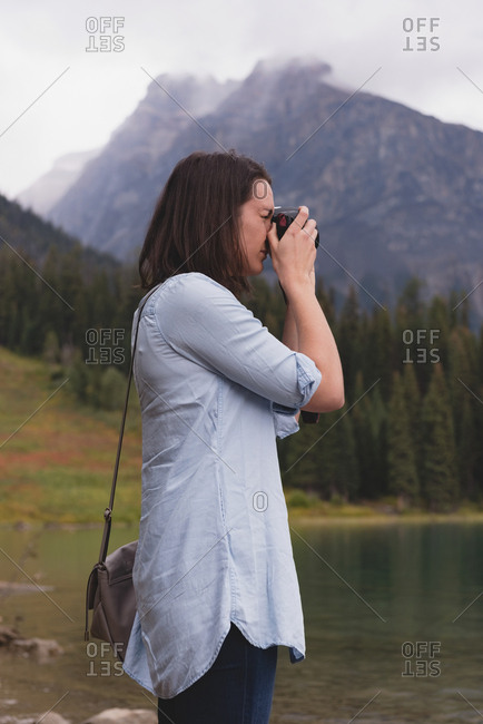 Side view of woman clicking photos with camera near lakeside