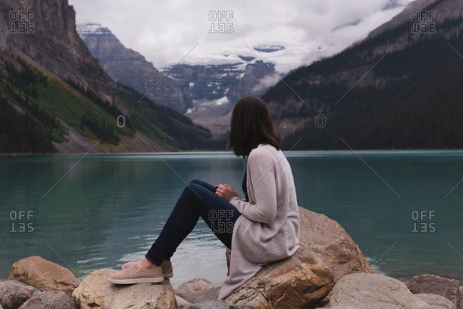 Side view of woman sitting on rock near lakeside