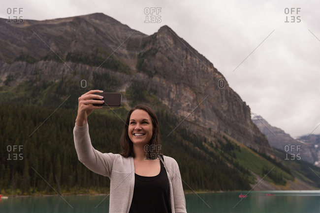 Happy woman taking selfie with mobile phone near lakeside