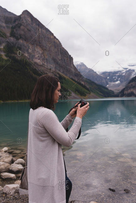 Side view of woman reviewing photos on camera near lakeside