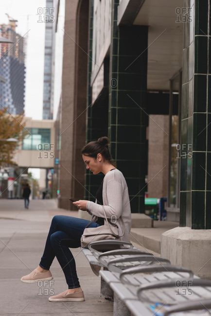 Beautiful woman using mobile phone in the city