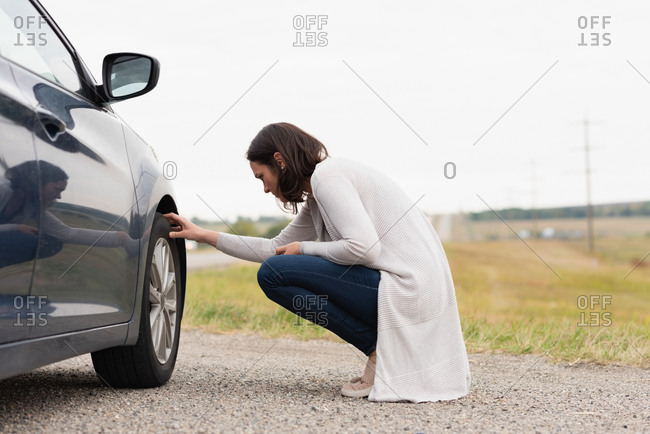 Side view of woman checking car tire during breakdown