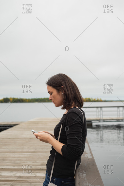 Woman using mobile phone on pier near riverside
