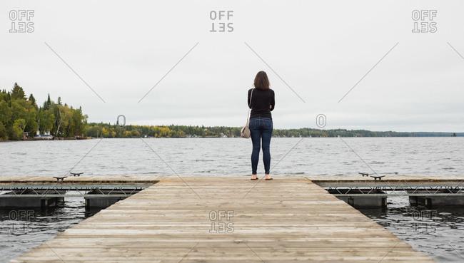 Rear view of woman standing on pier near riverside