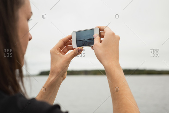 Close-up of woman clicking photos with mobile phone near riverside