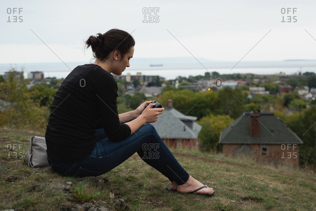 Side view of woman reviewing photos on camera