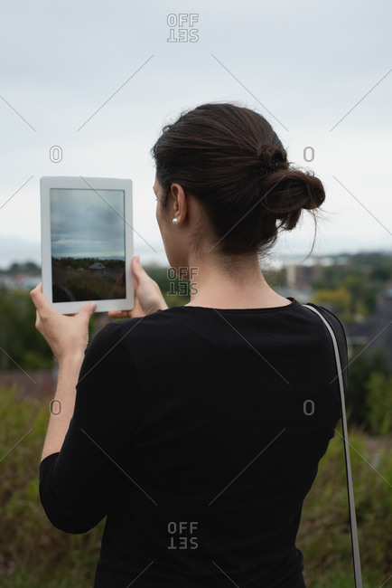 Rear view of woman clicking photos with digital tablet