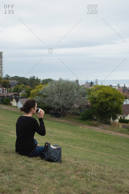 Rear view of woman having coffee while sitting on a hill