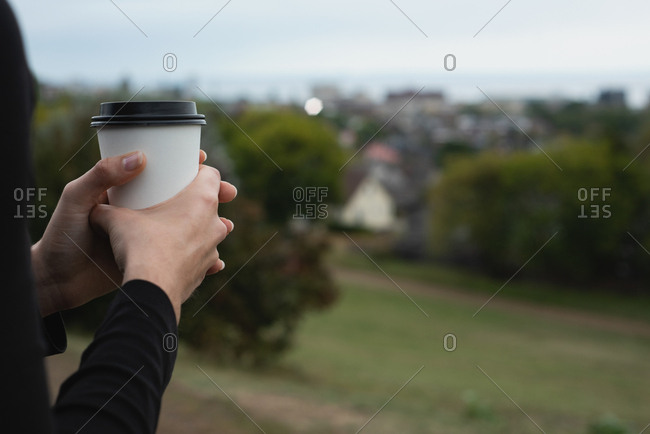 Mid section of woman holding coffee cup on a hill