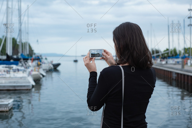 Rear view of woman clicking photos with mobile phone near harbor