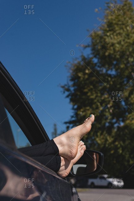 Low section of woman relaxing with feet up in a car