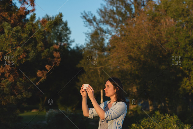 Beautiful woman clicking photos with mobile phone near riverside