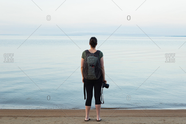 Rear view of woman standing with backpack and camera on the beach