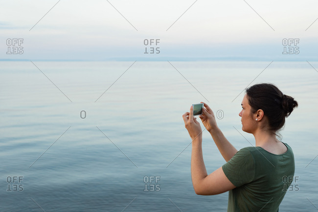 Side view of woman clicking photos with mobile phone