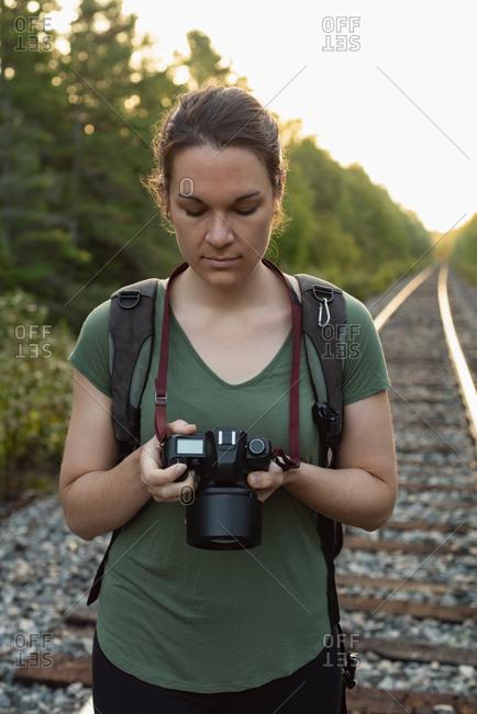 Beautiful woman reviewing photos on digital camera