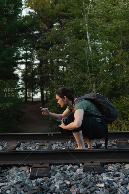Woman clicking photos with mobile phone on railway track