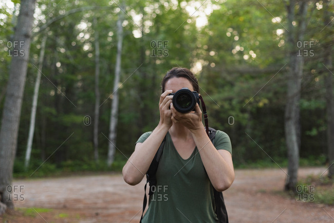 Woman clicking photos with camera in forest