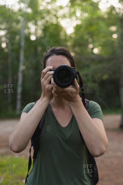 Close-up of woman clicking photos with camera in forest