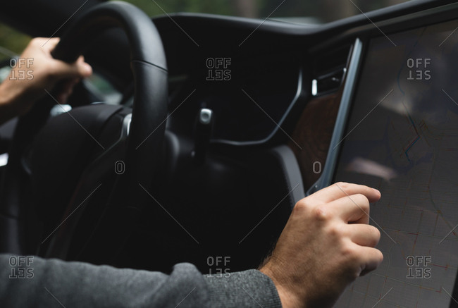 Close-up of man using navigator map while driving a car