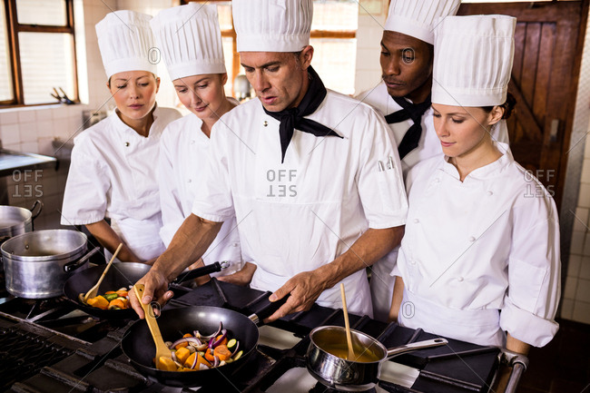 Head chef teaching his team to prepare a food in kitchen