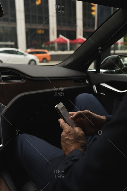 Mid section of businessman using mobile in car