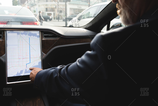 Mid section of businessman using navigator map while driving a car