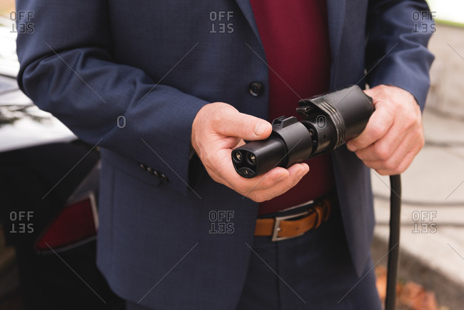 Mid section of businessman holding plug of charger at charging station