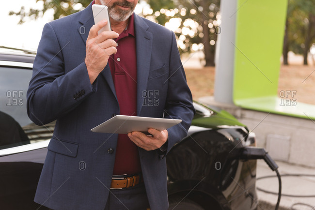 Mid section of businessman using digital tablet while talking on mobile phone