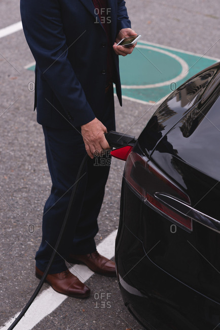 Low section of businessman using mobile phone while charging electric car